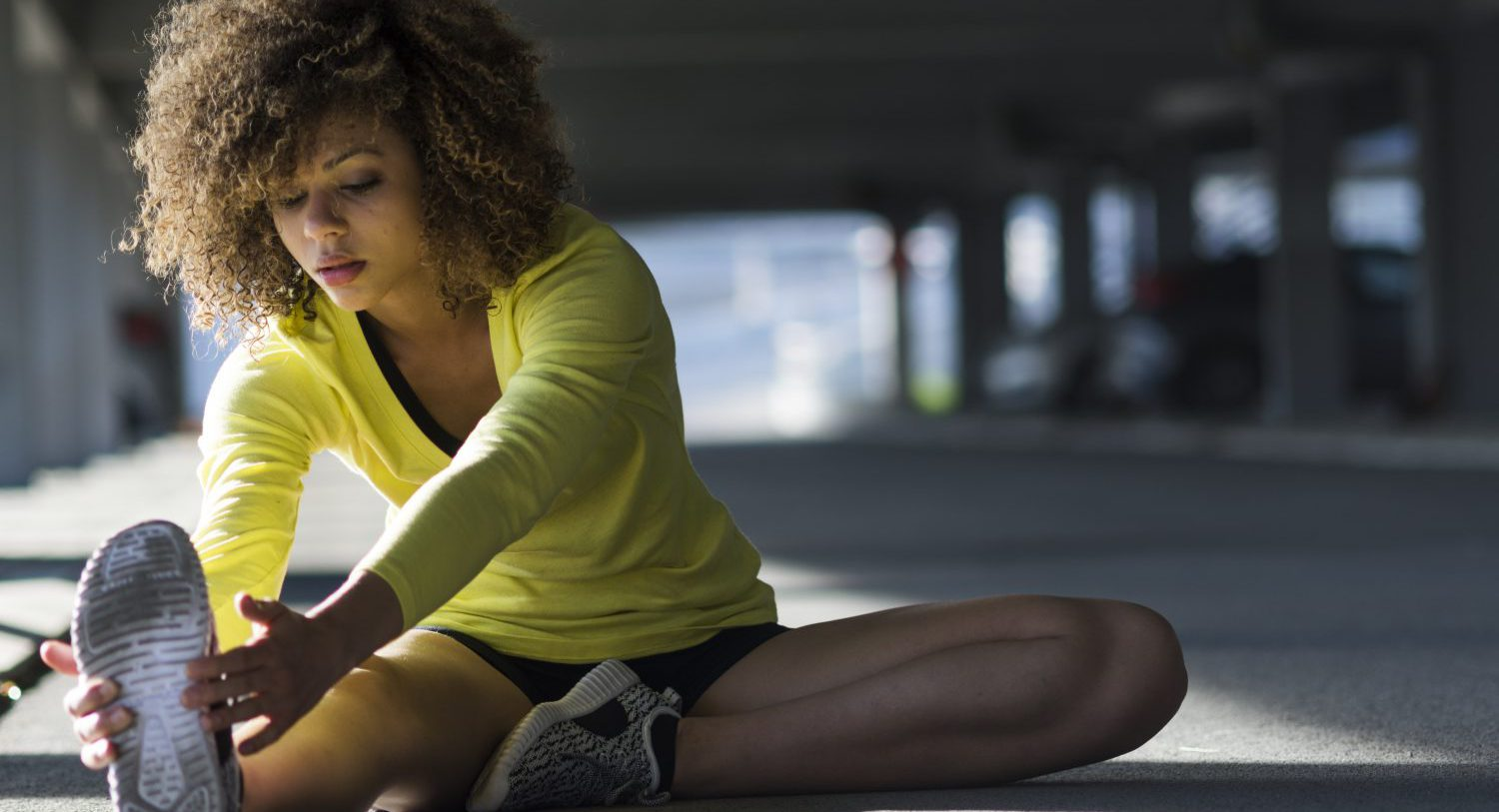 Woman stretching and listening to the music on her headphones