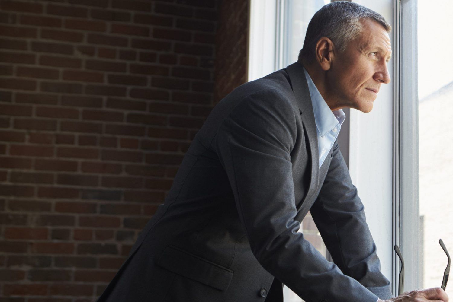 Mature Businessman Standing By Office Window With Coffee