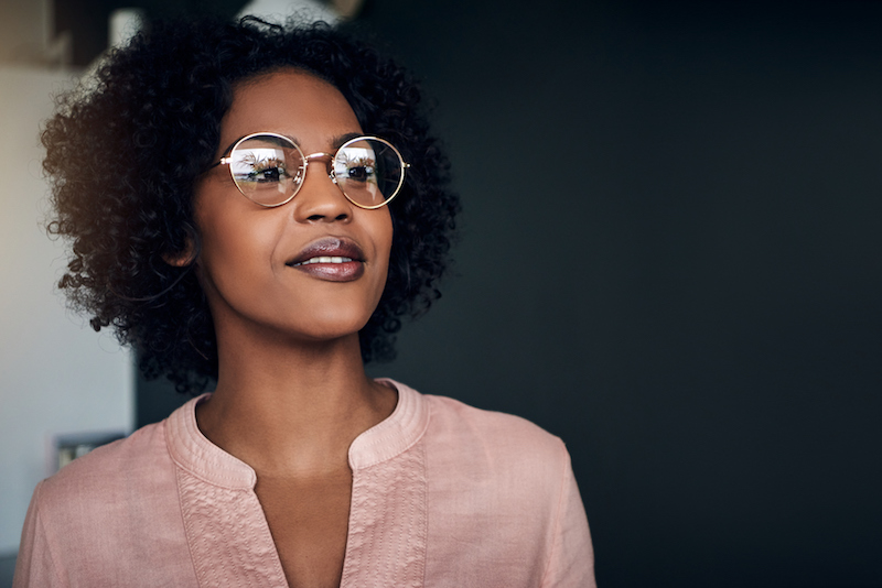 Smiling businesswoman wearing glasses looking deep in thought while standing alone in a modern office