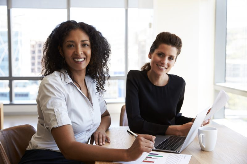 Portrait Of Two Businesswomen With Laptop Computer In Office